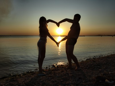 photo of couple on beach at sunset making heart shape with their arms
