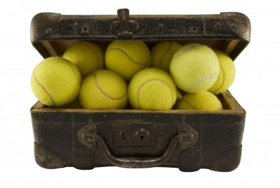 picture of old suitcase filled with tennis balls