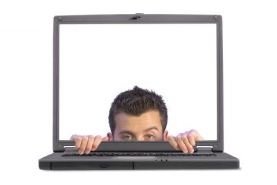 young man's head peeking out of computer